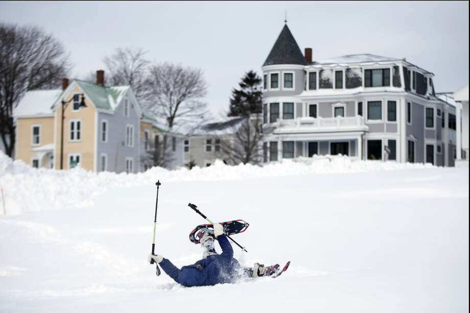 After several failed attempts to get up after falling in a deep snowdrift on the Eastern Promenade, Sandy Asmussen, 65, rolls over on her back to frees her snowshoes, Wednesday, Jan. 28, 2015, in Portland, Maine. (AP Photo/Robert F. Bukaty)