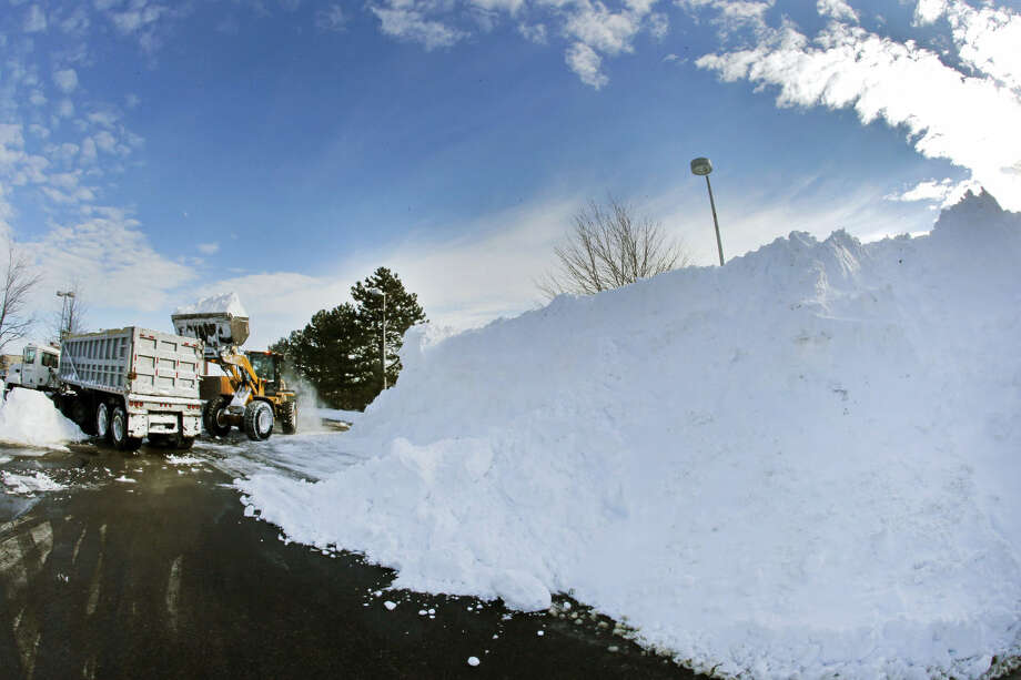 Workers remove snow from a mall parking lot, Wednesday, Jan. 28, 2015, in Methuen, Mass., after a blizzard dumped over 2 feet of snow in some areas of the Merrimack Valley. (AP Photo/Elise Amendola)