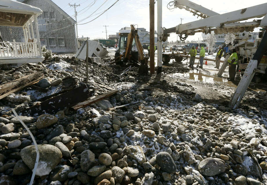 Utility crews make repairs amid stones and debris the day after a winter storm in Marshfield, Mass., Wednesday, Jan. 28, 2015. (AP Photo/Michael Dwyer)