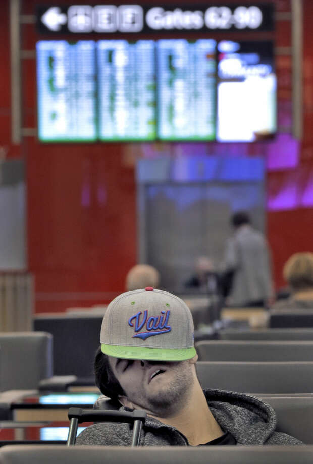 A passenger sleeps while waiting for a flight Tuesday, Jan. 27, 2015, at the Tampa International Airport in Tampa, Fla. Most flights out of Tampa to the northeast are canceled due to major storm dumping several inches of snow in the area. (AP Photo/Chris O'Meara)