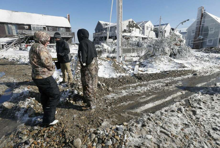 Sand, rocks and debris cover the road in front damaged houses the day after a winter storm in Marshfield, Mass., Wednesday, Jan. 28, 2015. The storm buried the Boston area in more than 2 feet of snow and lashed it with howling winds that exceeded 70 mph. (AP Photo/Michael Dwyer)