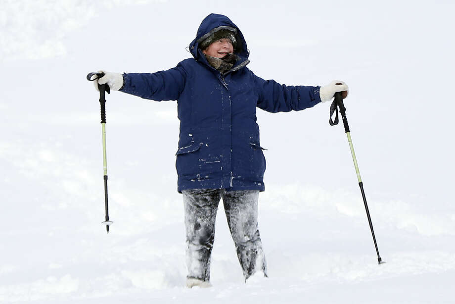 "Sandy Asmussen, 65, celebrates after finally getting herself upright after falling in a deep snowdrift while snowshoeing, Wednesday, Jan. 28, 2015, in Portland, Maine. Asmussen, who has had one hip replaced three times and the other hip replaced once, rejected offers of help during her ordeal. ""You gotta stay active,"" she said. (AP Photo/Robert F. Bukaty)"