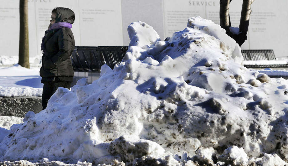 A pedestrian walks past a large pile of snow and ice on North Washington Avenue on Wednesday, Jan. 28, 2015 in Scranton, Pa. (AP Photo/The Scranton Times-Tribune, Butch Comegys) MANDATORY CREDIT