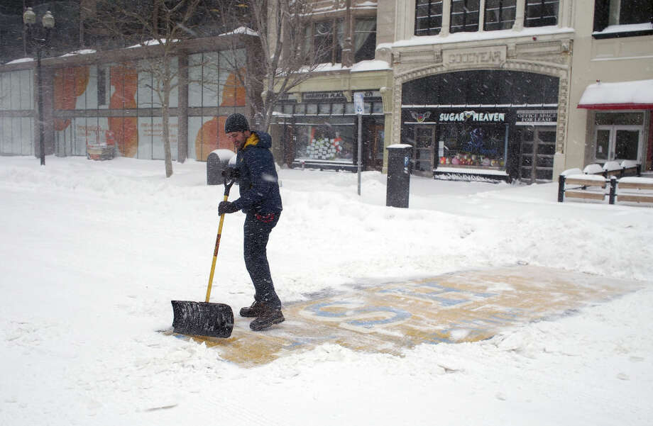 In this Tuesday, Jan. 27, 2015, photo provided by Adam Reynolds, Chris Laudani, a bartender at the Back Bay Social Club, shovels snow from the Boston Marathon finish line on Boylston Street, in Boston, during a winter storm that slammed eastern Massachusetts with as much as 2 feet of snow. (AP Photo/Adam Reynolds)