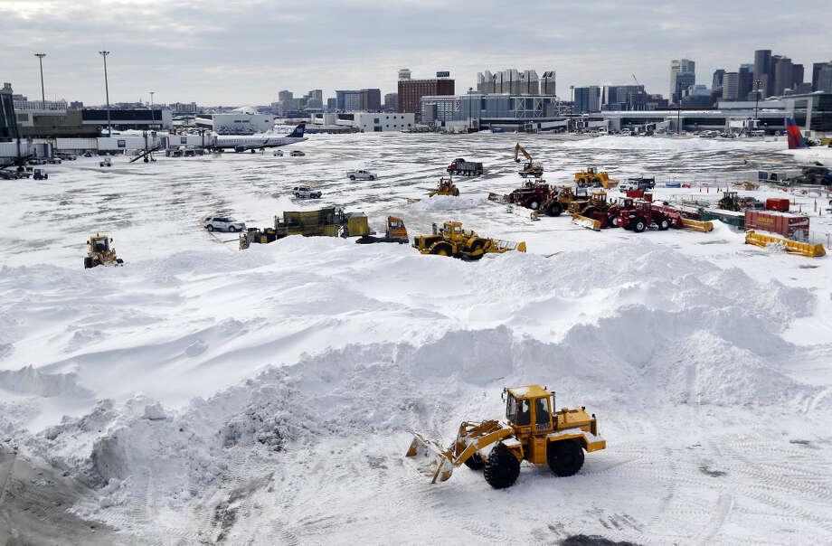 Workers move snow into a large pile for melting at a gate area of Logan International Airport in Boston Wednesday, Jan. 28, 2015, one day after a blizzard dumped about two feet of snow in the city. (AP Photo/Elise Amendola)