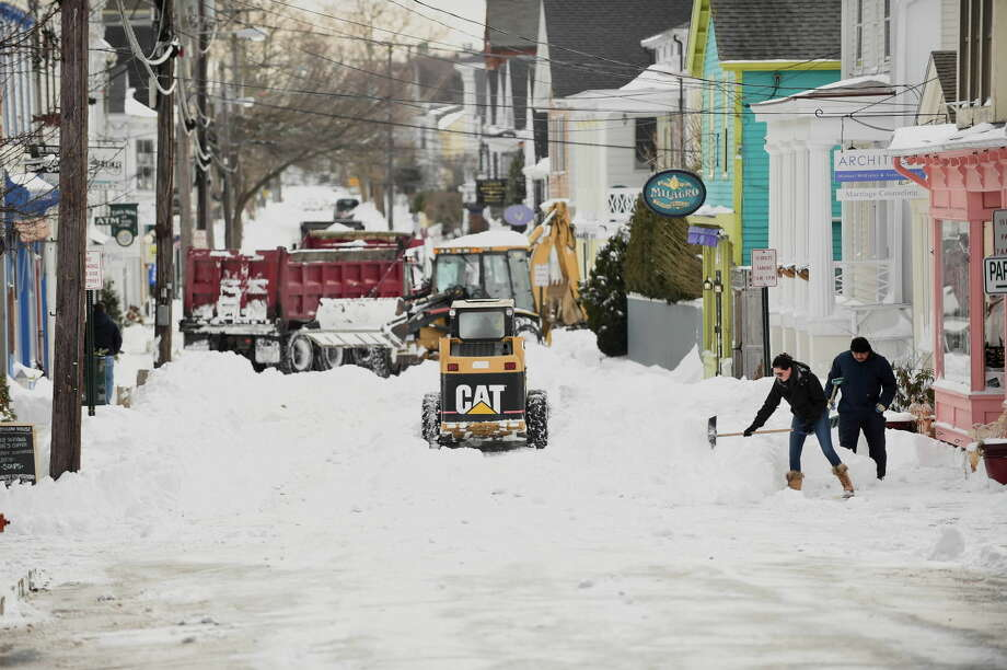 Megan Coon shovels snow from a sidewalk after a winter storm, Wednesday, Jan. 28, 2015, in Stonington, Conn. The storm buried the Boston area in more than 2 feet of snow and lashed it with howling winds that exceeded 70 mph. (AP Photo/The Hartford Courant, Cloe Poisson)
