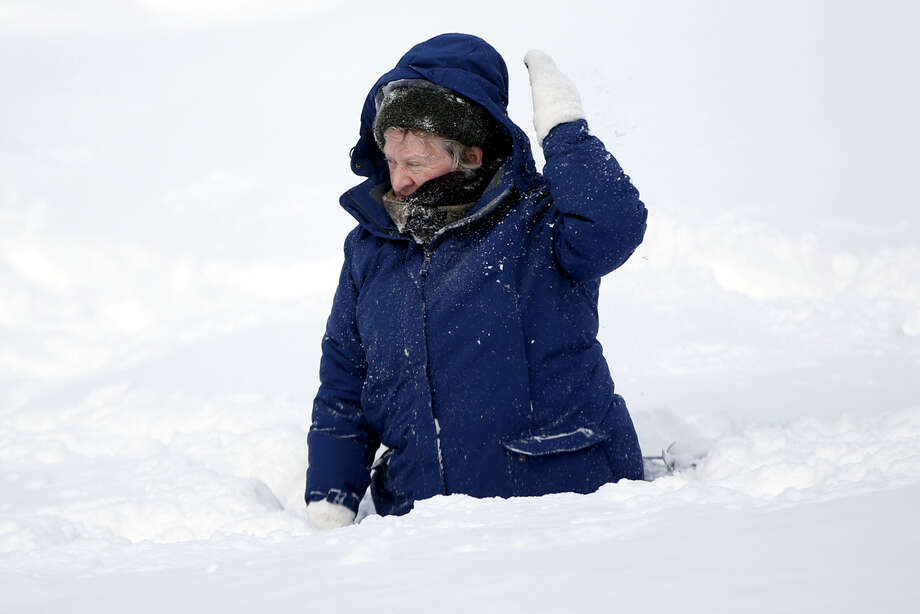 Sandy Asmussen, 65, brushes off some snow after falling face first in a deep snowdrift while snowshoeing on the Eastern Promenade in Portland, Maine, following a winter storm Wednesday, Jan. 28, 2015. Tuesday's blizzard dumped about two feet of snow in Portland. (AP Photo/Robert F. Bukaty)