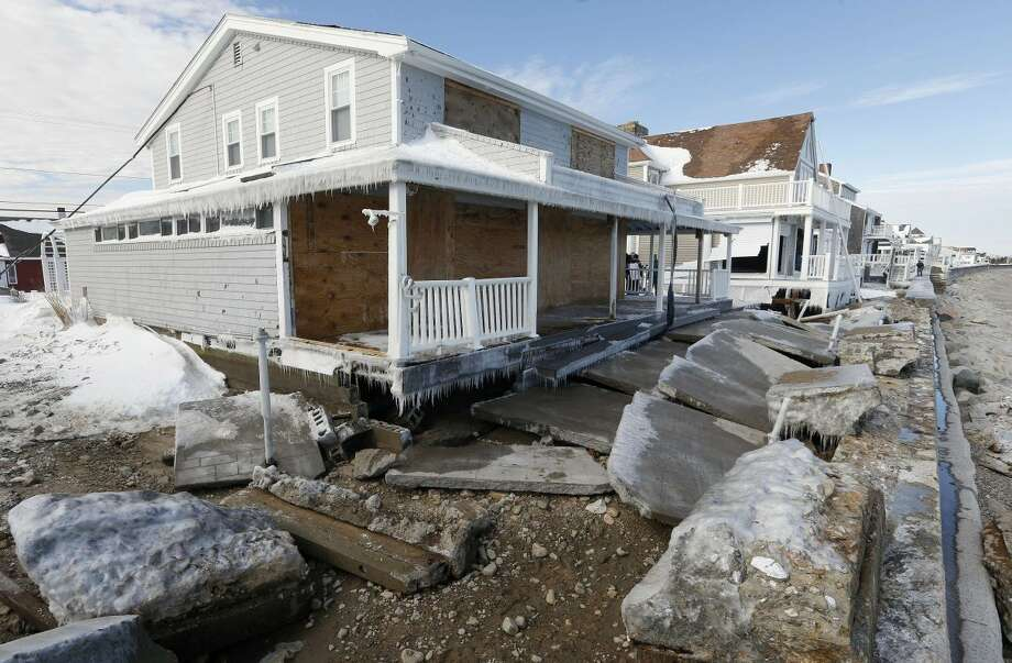 Concrete from a broken sea wall lies on the ground in front of damaged houses the day after a winter storm in Marshfield, Mass., Wednesday, Jan. 28, 2015. (AP Photo/Michael Dwyer)