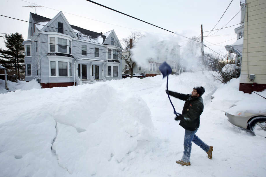 Tyler Whitney throws a load of snow on top of a growing snowbank in front of his home while shoveling out after a winter storm, Wednesday, Jan 28, 2015, in Portland, Maine. Tuesday's blizzard dumped about two feet of snow in Portland. (AP Photo/Robert F. Bukaty)