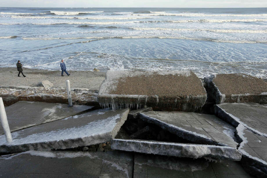A couple walks on the beach below a damaged seawall the day after a winter storm, Wednesday, Jan. 28, 2015, in Marshfield, Mass. The storm punched out a 40-to-50-foot section of a seawall. (AP Photo/Michael Dwyer)