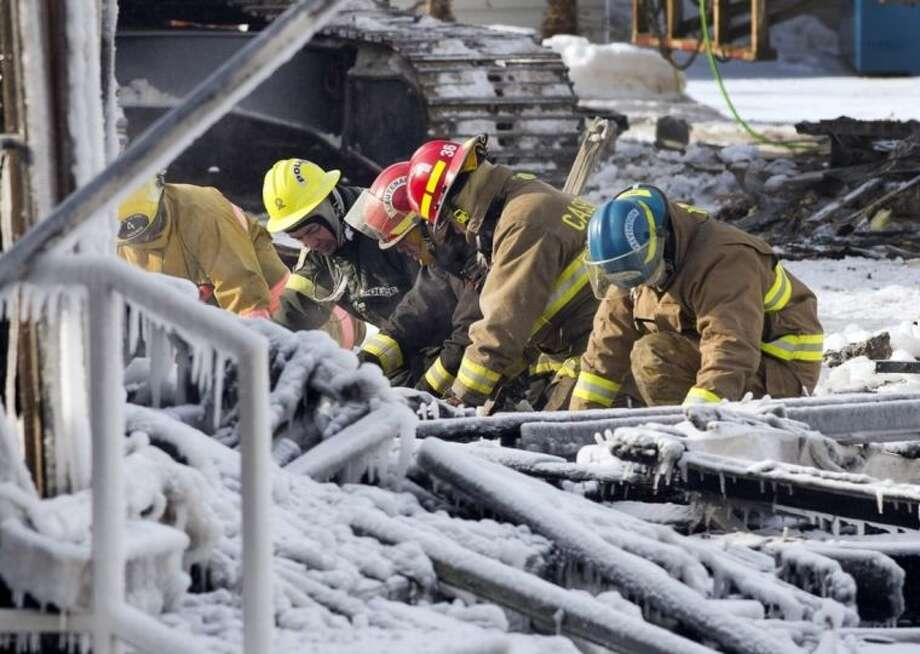 Rescue personeel search through the icy rubble of fire that destroyed a seniors' residence Friday, Jan. 24, 2014, in L'Isle-Verte, Quebec. Five people are confirmed dead and 30 people are still missing, while with cause of Thursday morning's blaze is unclear police said. Authorities are using steam to melt the ice and to preserve any bodies that are buried. (AP Photo/The Canadian Press, Ryan Remiorz)