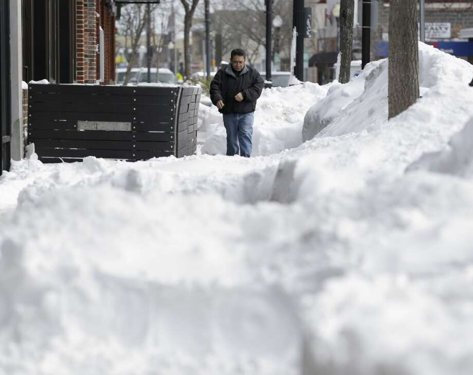 A man walks on a path cleared through the snow in Patchogue, N.Y., Wednesday, Jan. 28, 2015. While much of the New York City region breathed easier after eluding serious damage from a deadly blizzard, highway crews helped eastern Long Island residents recover from a storm that dumped more than two feet of snow in some places. (AP Photo/Seth Wenig)