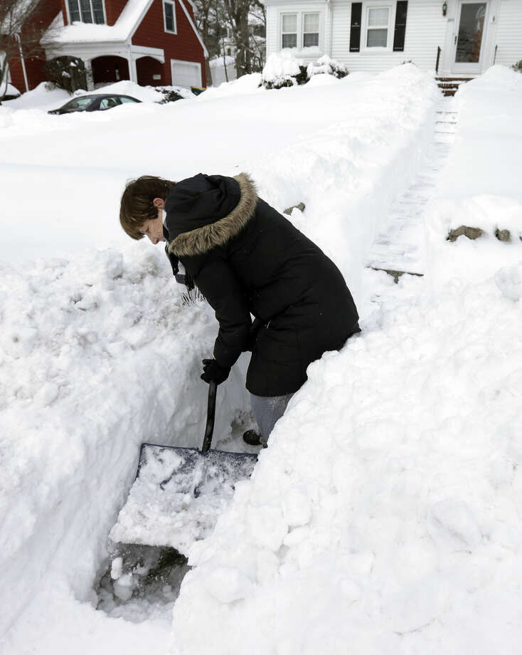 Phyllis Brent clears a path so the mailman can reach her home, Wednesday, Jan. 28, 2015, in Norwood, Mass., after a winter snowstorm slammed New England on Tuesday. (AP Photo/Steven Senne)