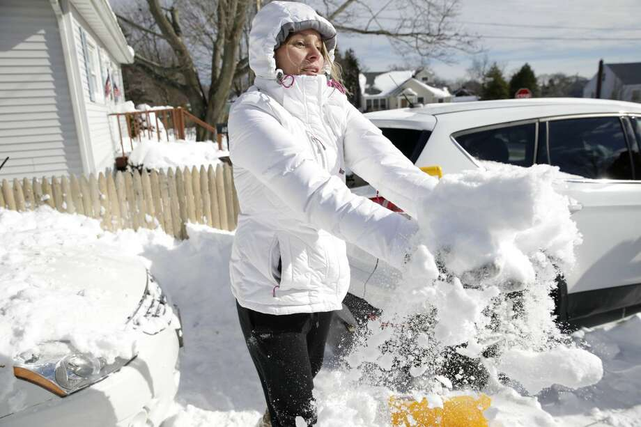 Kate Perry helps her brother and sister-in-law clear snow from their cars in Patchogue, N.Y., Wednesday, Jan. 28, 2015. While much of the New York City region breathed easier after eluding serious damage from a deadly blizzard, highway crews helped eastern Long Island residents recover from a storm that dumped more than two feet of snow in some places. (AP Photo/Seth Wenig)