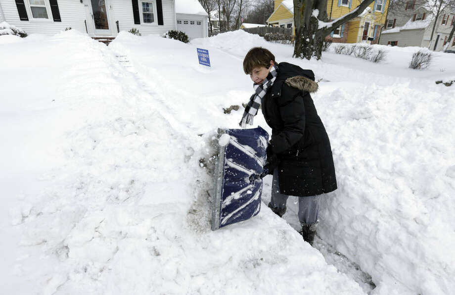 Phyllis Brent clears a path so the mailman can reach her home Wednesday, Jan. 28, 2015, in Norwood, Mass., after a winter snowstorm slammed New England on Tuesday. (AP Photo/Steven Senne)