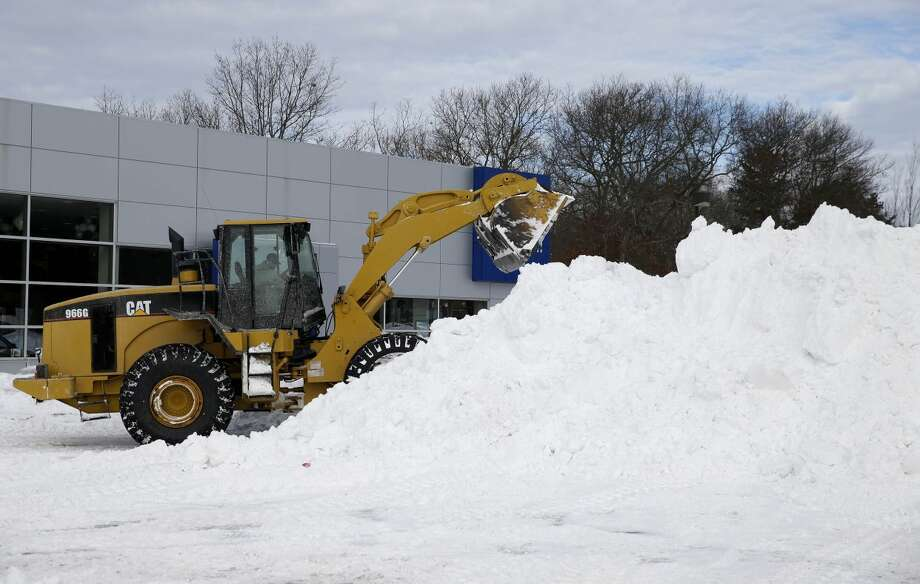 The snow from a car dealership is collected in a large pile to be trucked away in Medford, N.Y., Wednesday, Jan. 28, 2015. While much of the New York City region breathed easier after eluding serious damage from a deadly blizzard, highway crews helped eastern Long Island residents recover from a storm that dumped more than two feet of snow in some places. (AP Photo/Seth Wenig)