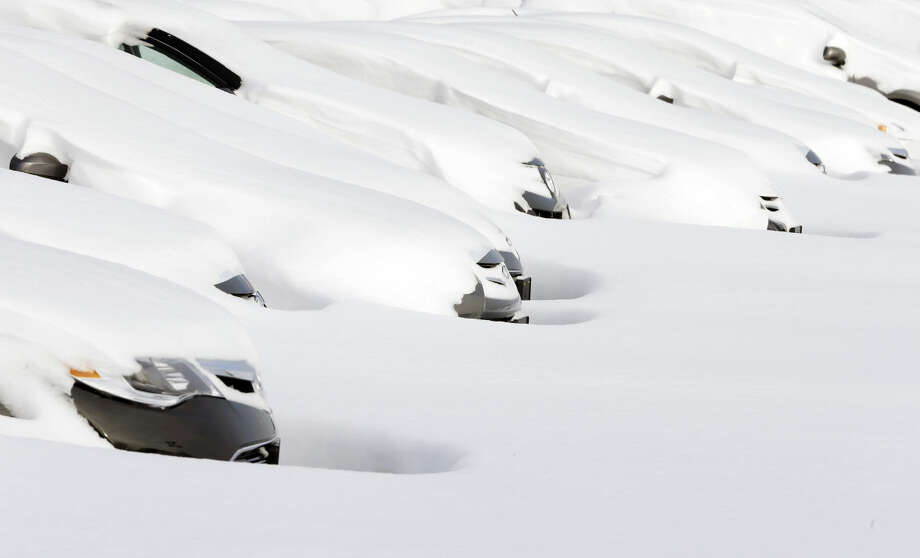 Cars sit buried by drifted snow Wednesday, Jan. 28, 2015, at a used auto dealer in Norwood, Mass., after a winter snowstorm slammed New England on Tuesday. The storm buried the Boston area in more than 2 feet of snow and lashed it with howling winds that exceeded 70 mph. (AP Photo/Steven Senne)