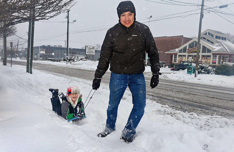 Hour photo / Erik Trautmann Carlos Sandoval and his son Diego make thei rway down Main St in Norwalk during Snowstorm Jonas on Saturday afternoon.