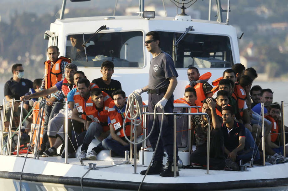 FILE - In this file photo taken on Wednesday, June 17, 2015, a Greek Coast Guard vessel arrives carrying migrants at the port of Mytilene, Greece, after a rescue operation on the northeast Greek island of Lesvos. NATO's European commander on Thursday, Feb. 11, 2016, ordered three warships to move immediately to the Aegean Sea to help end the deadly smuggling of migrants between Turkey and Greece. (AP Photo/Thanassis Stavrakis, File)