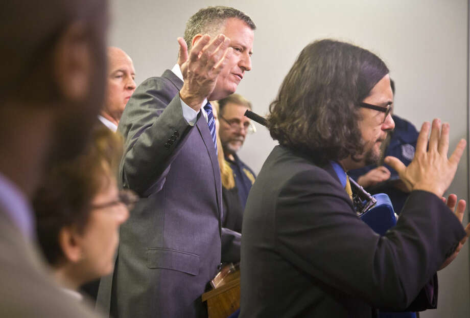 A sign language intrepeter signs as New York City Mayor Bill de Blasio, center, hold a press conference surrounded by top city officials at the city's Office of Emergency Management, Monday, Jan. 26, 2015, in New York. De Blasio says streets will be closed to all but emergency vehicles starting at 11 p.m. Monday ahead of the expected 18 to 24 inches of snow. (AP Photo/Bebeto Matthews)