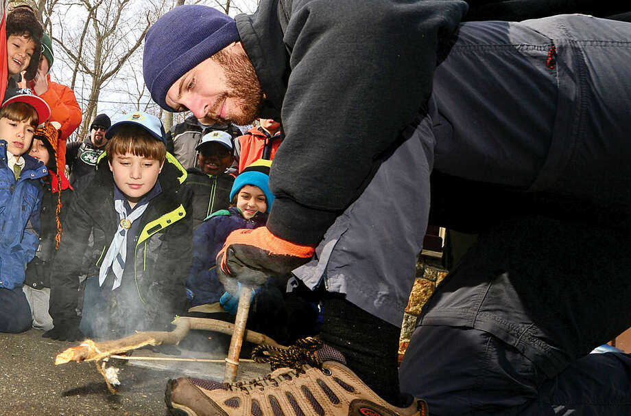 "Stamford Museum educator Daniel Brubaker shows Cub Scouts including Matthew West how to start a fire with a bow drill as the Boys Scouts of America hold their ""Cub Scout Winter Wild"" at the Stamford Museum & Nature Center Saturday."
