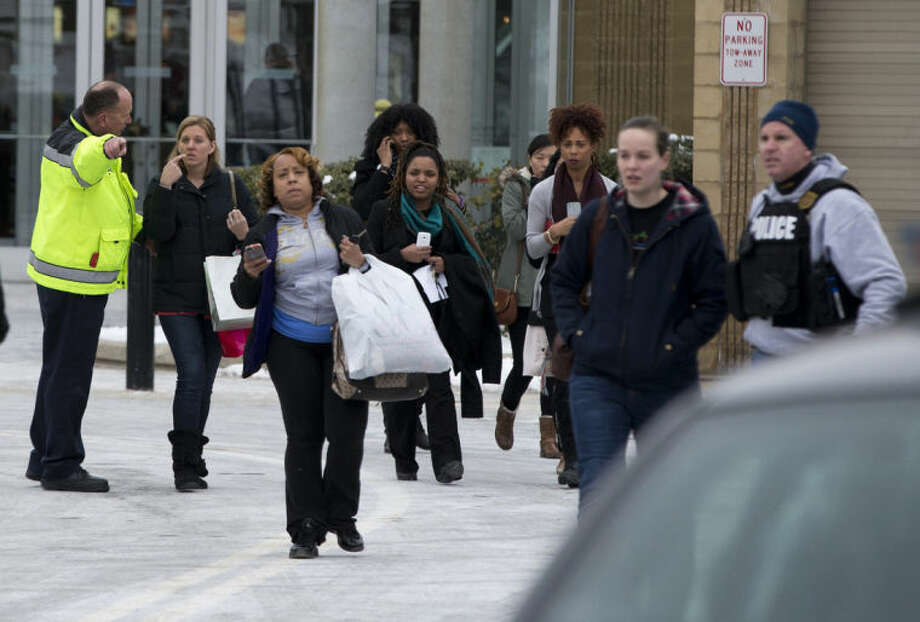 Police and law enforcement evacuate tTe Mall of Columbia after a shooting on Saturday, Jan. 25, 2014 in Columbia, Md. Police say three people died in a shooting at the mall in suburban Baltimore, including the presumed gunman. (AP Photo/ Evan Vucci)