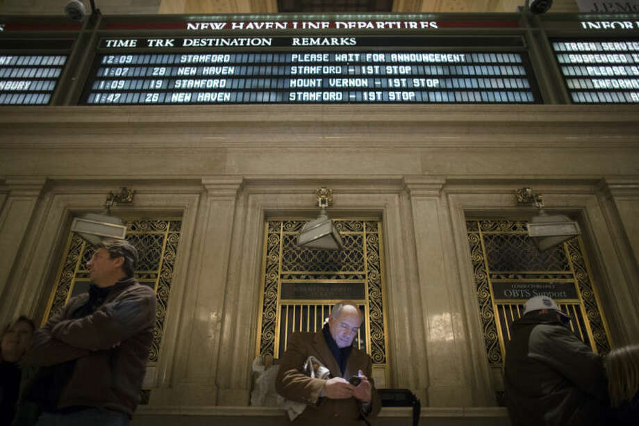 A commuter stands beneath the New Haven train line schedule display in the main hall of Grand Central Station as hundreds wait after a power problem with Metro-North Railroad's computer system caused the suspension of service on the Hudson, Harlem, and New Haven lines, Thursday, Jan. 23, 2014, in New York. Trains were brought to a halt for safety purposes while electricians worked to hook up temporary power to the computer system. Metro-North is the nation's second-busiest railroad and serves 281,000 riders a day in New York and Connecticut. (AP Photo/John Minchillo)