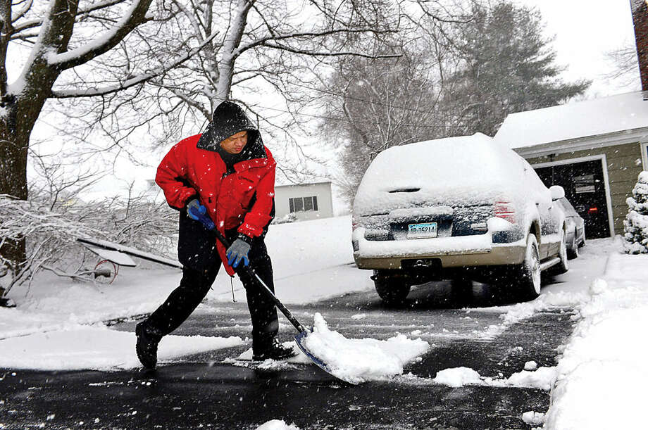 Hour photo / Erik Trautmann Kevin Aguiar clears his driveway on King St. during the Friday snow storm in Norwalk.