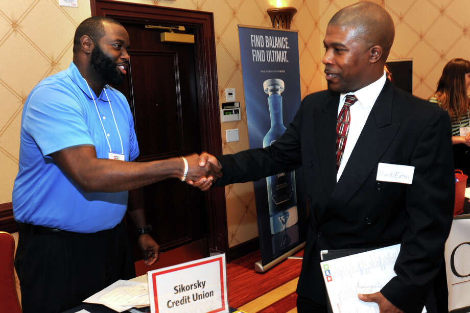 Shaune Rogers, left, a recruiter from Sikorsky Credit Union greets Mark Eaton, of Bridgeport, during the RecruitCT Job Fair held at the Trumbull Marriott, in Trumbull, Conn. June 10, 2016. Photo: Ned Gerard / Hearst Connecticut Media / Connecticut Post