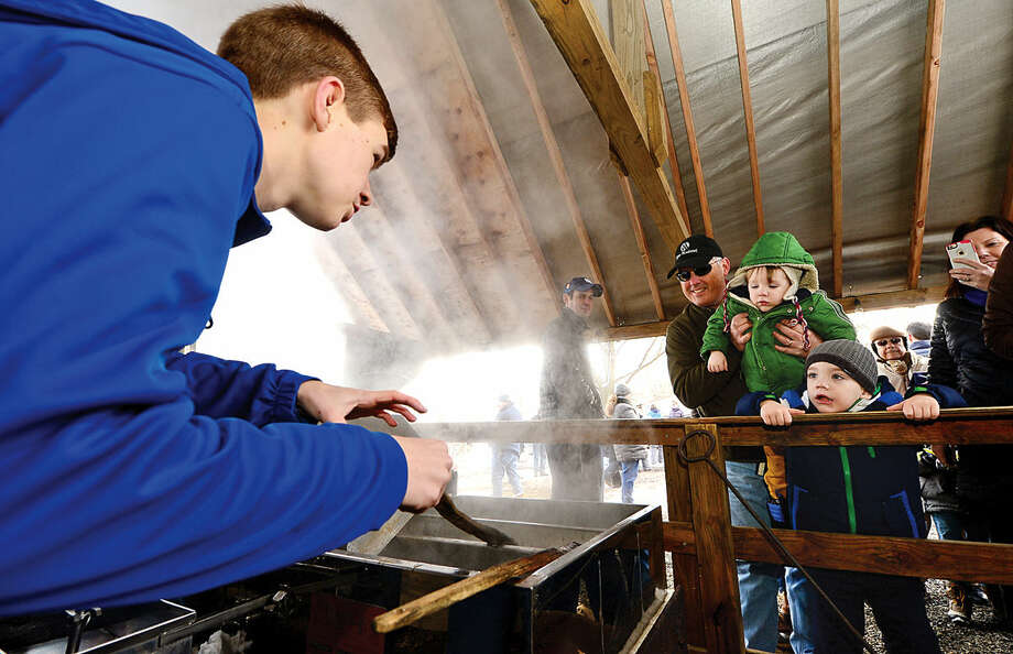 Hour photo / Erik Trautmann Ambler Farm volunteer Jay Kineon shows as local residents they reduce Maple sap to make syrup during the annual Ambler Farm Maple Syrup Program Saturday.