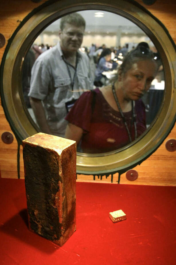 FILE - In this Aug. 10, 2010 file photo, coin collector Darlene Corio, of Rochester, N.Y., right, peers through a circular window at a gold ingot weighing more than 662 ounces as her husband, Tim Corio, left, looks on at a display at the World's Fair of Money in Boston. The ingot was among two tons of California Gold Rush gold recovered from the shipwreck of the S.S. Central America which sank in 1857. The U.S. Marshals Service captured former fugitive Tommy Thompson at a Hilton hotel in West Boca Raton on Tuesday Jan. 27, 2015. Thompson had been on the lam for two years, accused of cheating investors out of their share of $50 million in gold bars and coins he had recovered from the 19th century shipwreck. (AP Photo/Steven Senne, File)