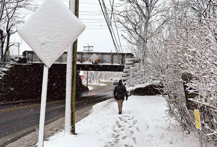Hour photo / Erik Trautmann Commuters make their way down East Ave. during the Friday snow storm in Norwalk.