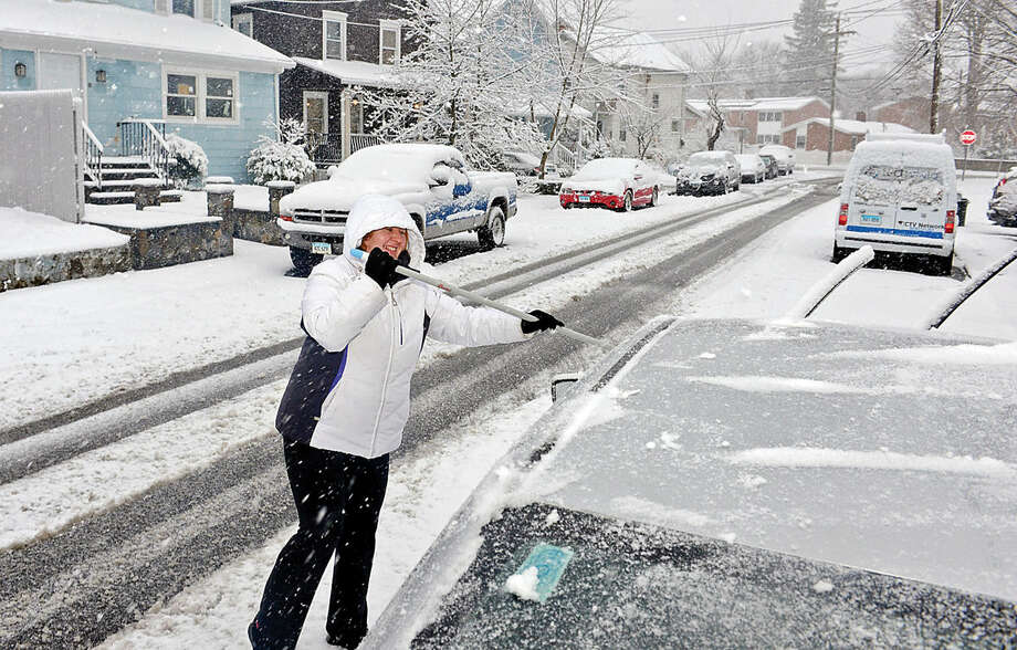 Hour photo / Erik Trautmann Cristina Daian clears snow from her car during the Friday snow storm in Norwalk.