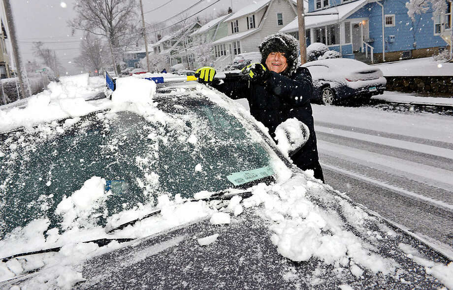 Hour photo / Erik Trautmann Jed Horowitz clears snow from his vehicle on Fifth St. during the Friday snow storm in Norwalk.