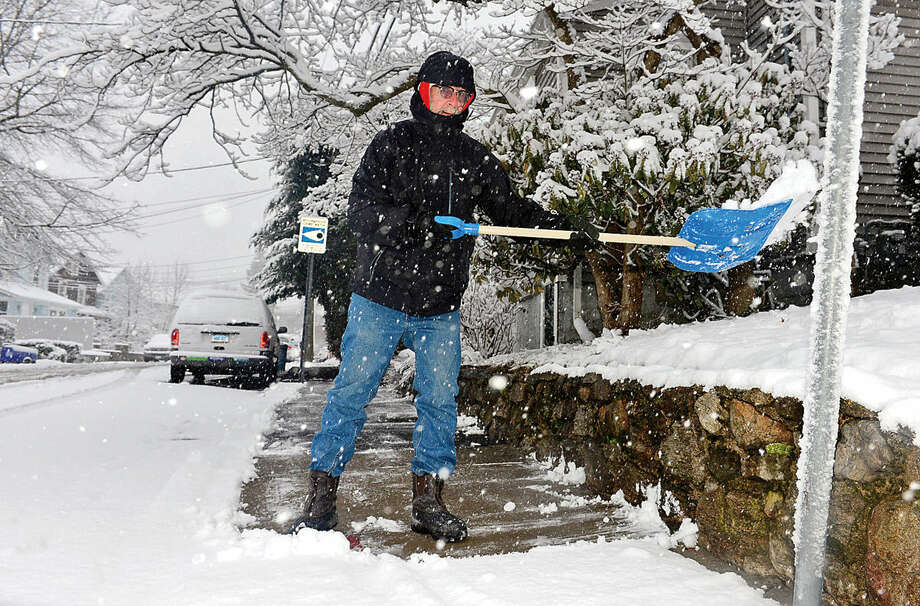 Hour photo / Erik Trautmann Frank Glick shovels his sidewalks on Camp St. during the Friday snow storm in Norwalk.