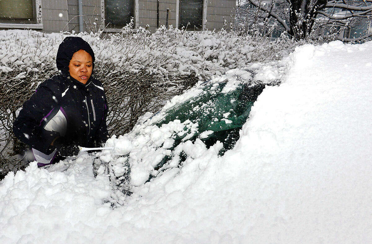 Hour photo / Erik Trautmann Vonie Pierre clears her car of snow during the Friday snow storm in Norwalk.