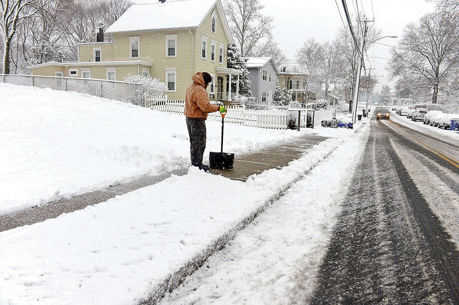 Hour photo / Erik Trautmann Norwalkers attempt to keep their sidewalks clear during the Friday snow storm in Norwalk.