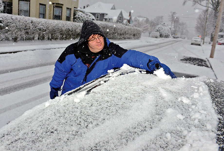 Hour photo / Erik Trautmann Dan Rankowitz clears snow from his car on Fifth St. during the Friday snow storm in Norwalk.