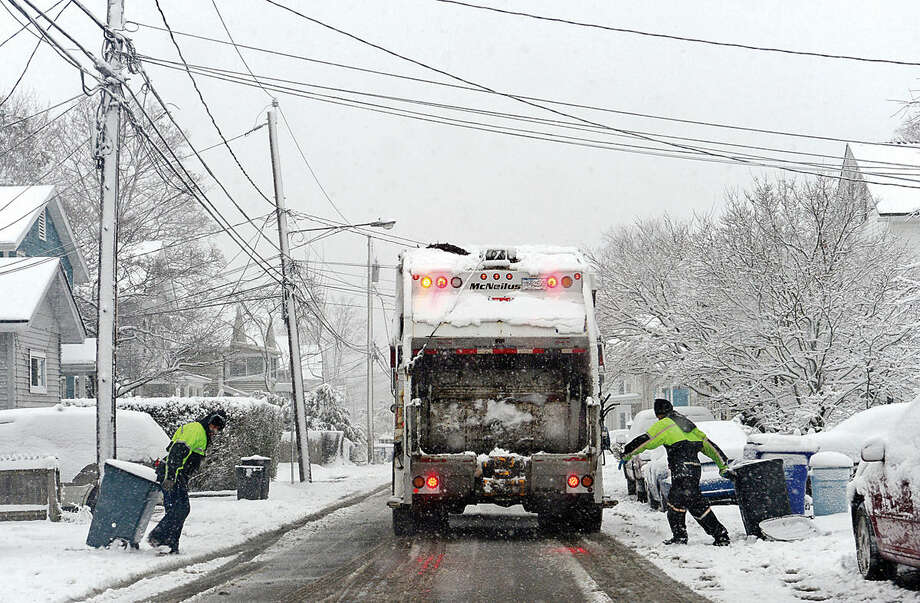 Hour photo / Erik Trautmann City Carting employees collect garbage during the Friday snow storm in Norwalk.