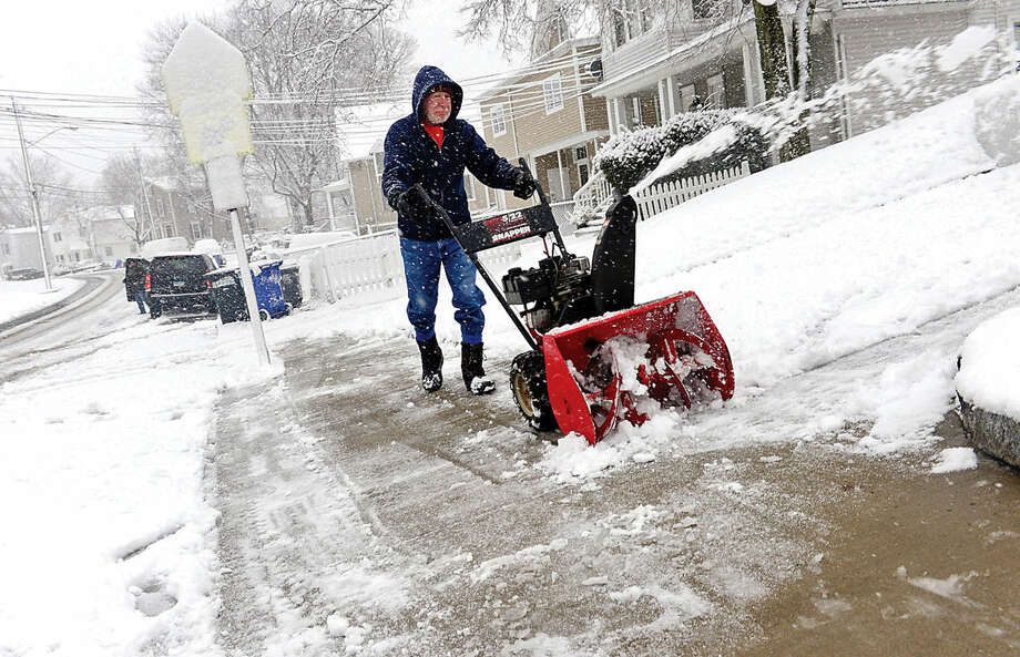 Hour photo / Erik Trautmann Bill Forcier blows snow from his sidewalk on Camp St during the Friday snow storm in Norwalk.
