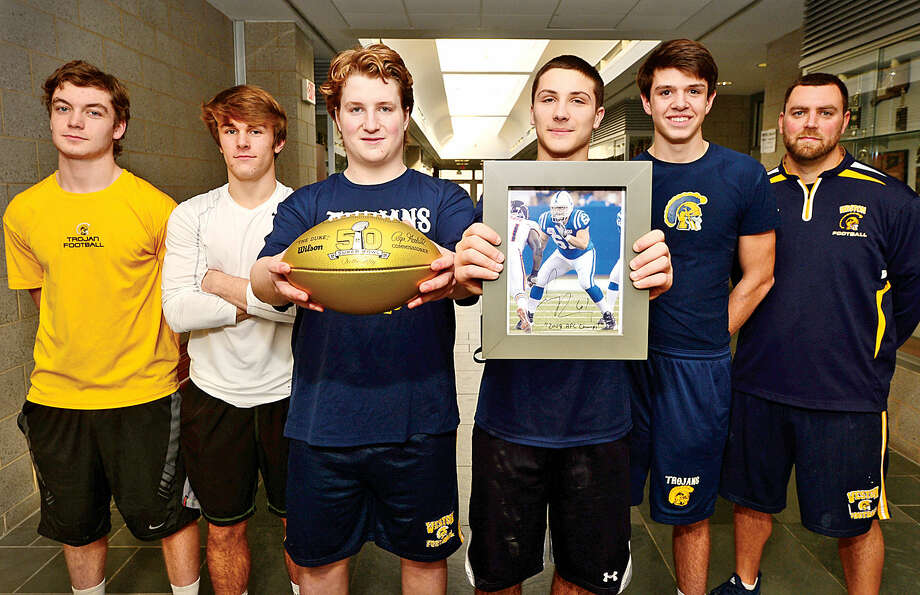 Hour photo / Erik Trautmann Weston High School football players Peter Achar, Alex Fruhbeis, Bobby Lummis, George Goetz, Matthew Oakes and coach Chris Pace display was a Golden Football from the NFL in honor of the 50th Super Bowl, Weston High School graduate and Super Bowl 44 player, Jamey Richard.