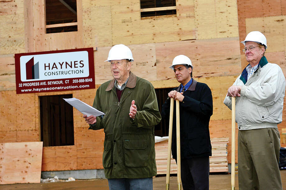 Wilton Commons resident George Ciaccio speaks during the ceremonial ground-breaking for the new building at Wilton Commons, while architect Louis Contadino and Wilton Commons board member, Buck Griswold, look on Wednesday.