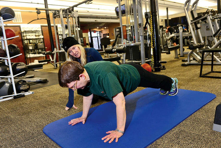 Trainer Lana Taubin works with client Moira Craw at Anytime Fitness in Wilton.