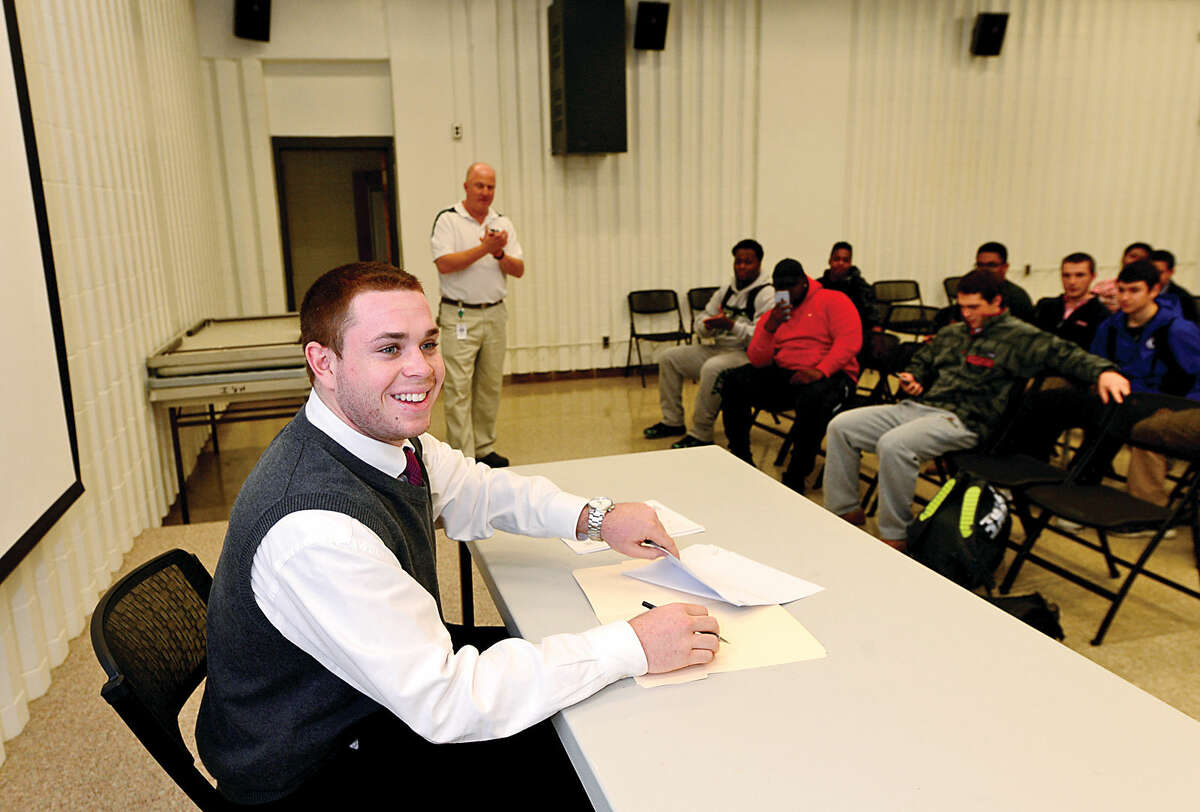 Hour photo / Erik Trautmann Norwalk High School senior and football stand out Eddie O'Hara signs his national letter of intent to play football at Bentley College while his teammates and Athletic Director Doug Marchetti look on during a brief ceremony Wednesday.