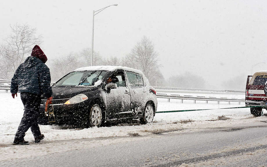 Hour photo / Erik Trautmann A passer by helps a stranded motorist that slid off the roadway on the Route 7 connector Friday morning.