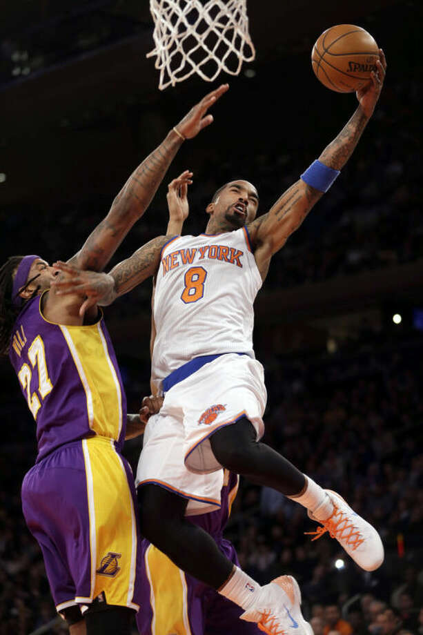 New York Knicks' J.R. Smith, right, goes for a basket over Los Angeles Lakers' Jordan Hill during the second half of an NBA basketball game at Madison Square Garden, Sunday, Jan. 26, 2014, in New York. The Knicks won 110-103. (AP Photo/Seth Wenig)