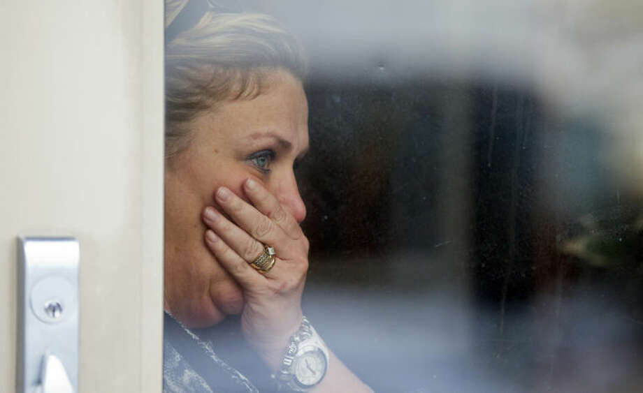 Restaurant general manager Heather Saffield, watches though the glass door from her restaurant at The Mall in Columbia Saturday, Jan. 25, 2014, in Columbia, Md., as police continue the evacuation of the remaining mall visitors following a shooting that police say three people died including the presumed gunman. (AP Photo/Manuel Balce Ceneta)