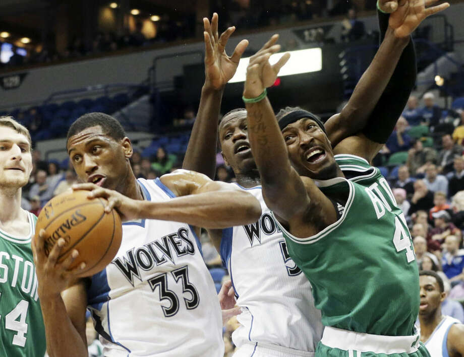 Minnesota Timberwolves' Thaddeus Young, left, beats Boston Celtics' Gerald Wallace, right, to the rebound in the first quarter of an NBA basketball game, Wednesday, Jan. 28, 2015, in Minneapolis. (AP Photo/Jim Mone)