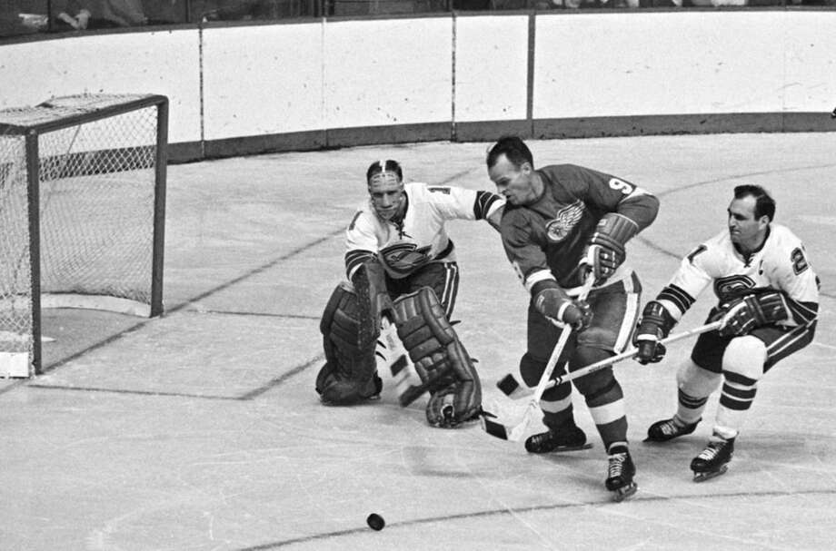 FILE - In this Oct. 26, 1967, file photo, California Seals goalie Charlie Hodge, left, knocks the puck away as Detroit Red Wings' star Gordie Howe tries a shot on goal as the Seals' Bob Baun comes in at right during the second period of an NHL hockey game in Detroit. Fifty years ago this week, the owners of the so-called Original Six unanimously approved doubling in size by awarding franchises to Los Angeles, San Francisco/Oakland, Philadelphia, Pittsburgh, St. Louis and Minneapolis/St. Paul. No other pro sports league had ever doubled its amount of teams, but the gamble proved to be one of the most important decisions in hockey history. (AP Photo/Preston Stroup, File)