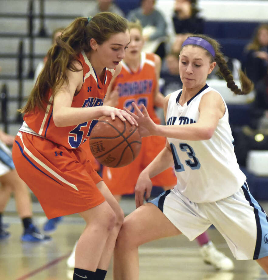 Hour photo/John Nash - Wilton's Makenna Pearsall, right, steals the ball from Danbury's Emily Broggy during Thursday's FCIAC girls basketball game in Wilton. The host Warriors won the game, 67-25.